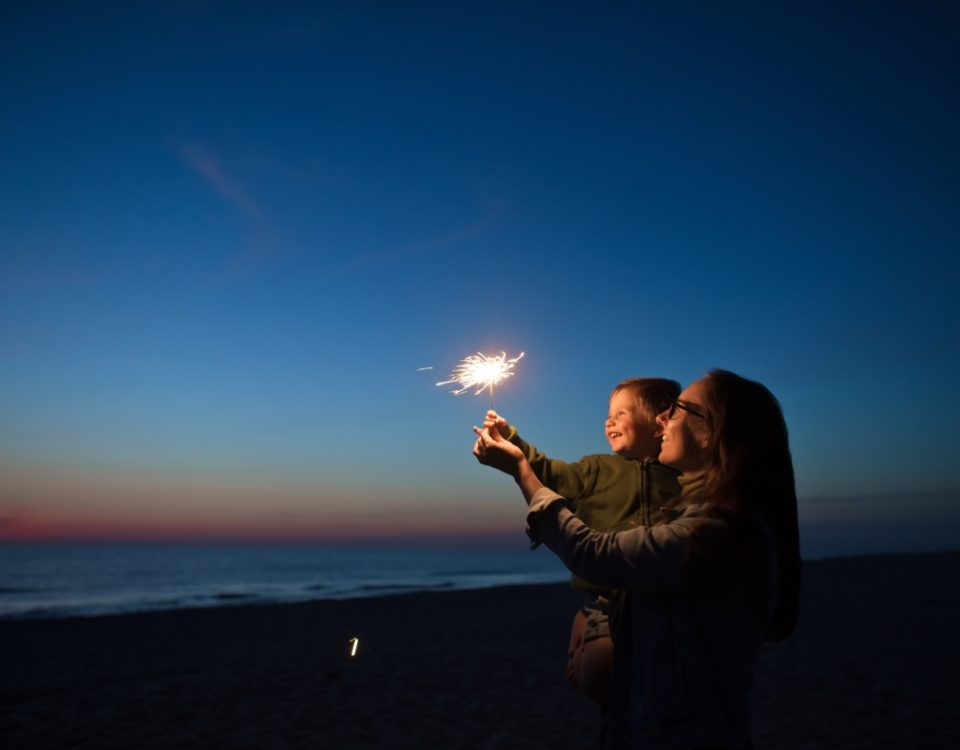 Mother and son holding sparkler in front of the beach at night.