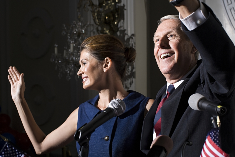 Politician and his wife waving to a crowd of supporters.